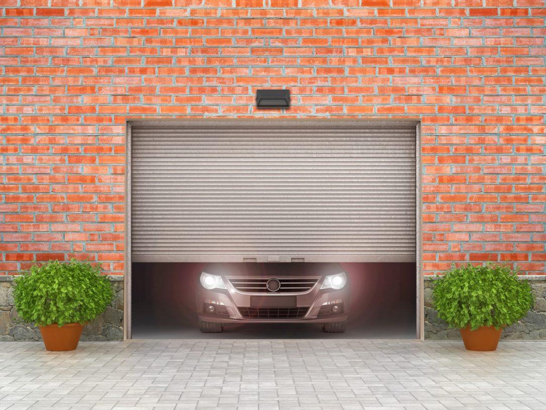 Fronten av en garasje med bil inne.